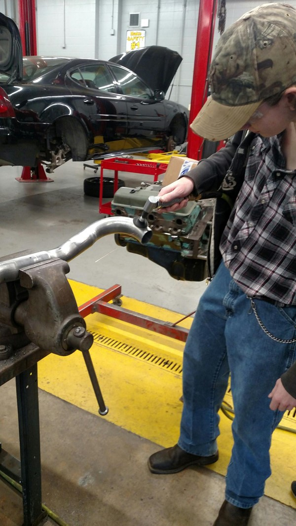 Automotive student working on muffler